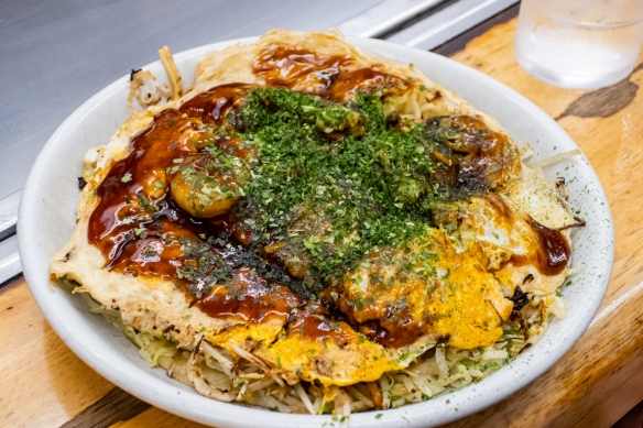The finished shrimp and pork okonomiyaki topped with shredded dried seaweed; Okonomimura, Hiroshima, Honshu Island, Japan