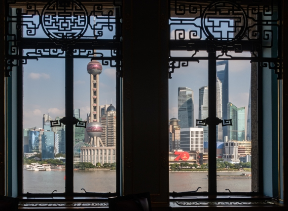 The view of the high-rise buildings in Pudong, across the Huangpu River, from the windows in the Dragon and Phoenix restaurant at the Fairmont Peace Hotel, Shanghai, China
