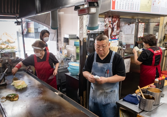 There was a staff of 5 or 6 to prepare the okonomiyaki (a savory pancake) on the hot griddles for a total of only about 14 seats (customers) at the L-shaped counters in front of the griddles, Okonomimura, Hiroshima, Honshu Island, Japan