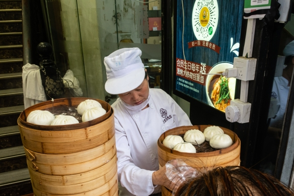 "This six-foot (two-meter) wide food stall on a side street off Nanjing Road Pedestrian Street sold only steamed buns (bao) – cooked upstairs -- and was doing a ""land mine"" business mid-afternoon, Shanghai, China"