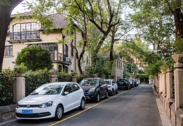 "An interesting street in the French Concession, Shanghai, China – the formerly private ""mansion"" homes on the left are now, again, individually privately owned by large companies, whereas the nearly identical buildings on the right are govermnt owned"