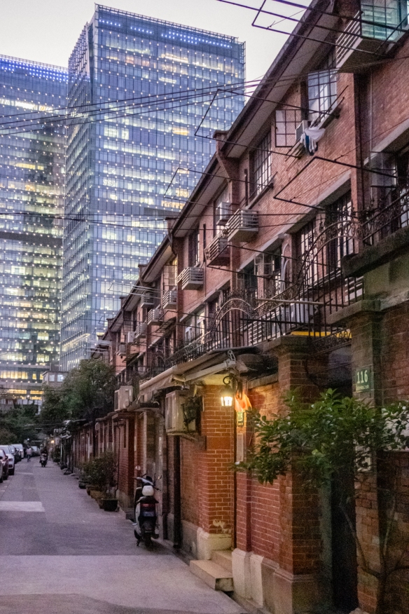 Typical low-rise early 20th century apartment buildings in the French Concession, Shanghai, China, flanked in the distance (outside the French Concession) by tall modern (21st century) high-rise apartment buildings