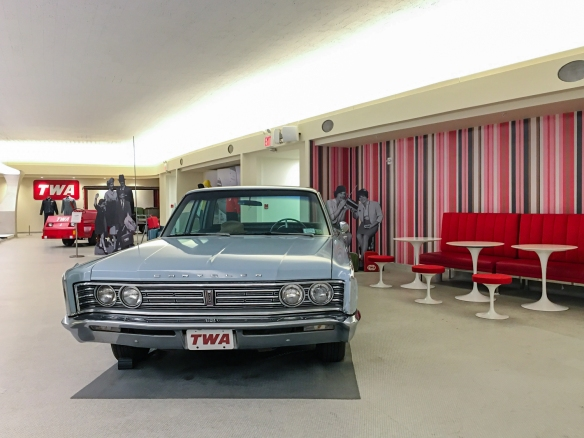 Outside the terminal (hotel) entrance there is a vintage Lincoln Continental parked for nostalgia – inside the terminal (hotel) by the snack and coffee stand is a 1960s Chrysler; TWA Hotel, JFK International Airport, New York, NY, USA