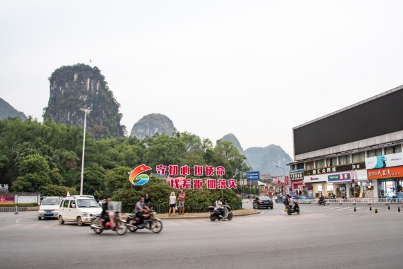The city of Yangshuo is the teriminus of the Li River scenic boat journeys through the Guilin karst mountains – here the mountains are visible behind a new shopping district; Guangxhi, China
