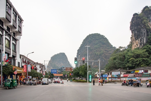 The Guilin karst mountains are very visible behind the city's main shopping street, Xi Jie Street (West Street), Yangshuo, Guangxhi, China