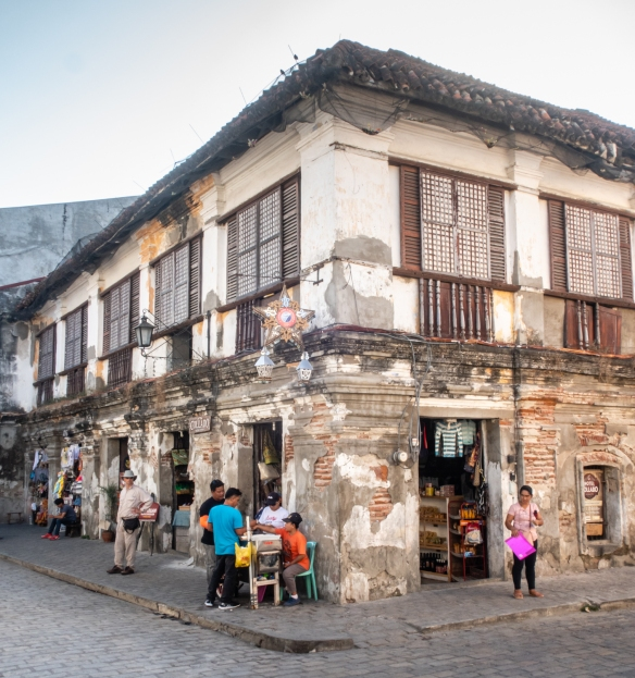 A typical historical two-story colonial, Spanish-influenced building along the main street of Vigan, Philippines, with retail stores on the ground floor and living spaces above