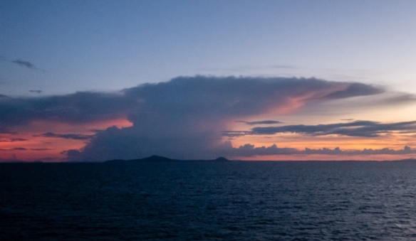 Light pinks light up the sky after sunset under a huge thunderhead cloud (with rain coming down) offshore of the Australian mainland; Lizard Island, Queensland, Australia