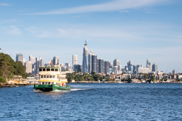 One of the numerous Sydney Ferries seen in White Bay with the modern skyline of the city behind it – the Millers Point and Wynyard neighborhoods (behind the normal view of downtown, seen from the center of Sydney Harbor and the Harbor Bridge